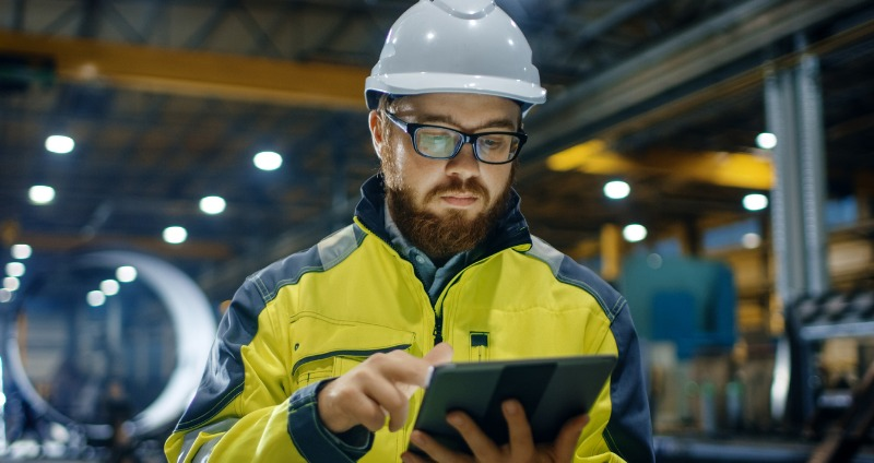 Engineer wearing safety gear holding a rugged laptop